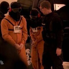 A hooded Hiro is led out of the van behind a hooded fugitive
