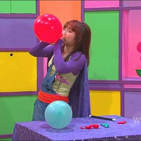 Sun Pezzimenti blowing a balloon