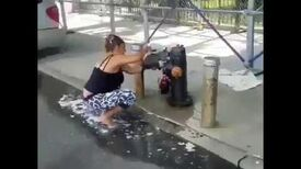 NYC Woman giving raccoon a shower in water hydrant