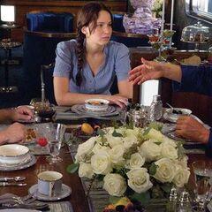 Haymitch déjeunant avec Katniss et Peeta dans le train pour le Capitole