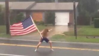 Florida crazy man challenges hurricane Matthew with American flag in hand.