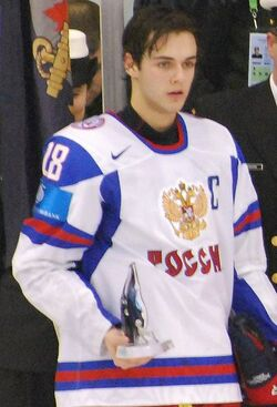 A young man with dark hair wearing a white jersey holds a small trophy in his right hand.