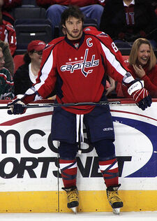 "An unshaven man with black hair stares into the distance. He is wearing a red uniform with blue pants and a logo saying ""Washington Capitals"" on his chest."