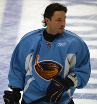 An ice hockey player is standing while slightly turned to his left.  He has short dark hair and is not wearing a helmet.  He is wearing a blue uniform with a large orange bird with a ice hockey stick on his chest.