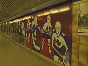 A mural at a subway platform of Toronto Maple Leafs players in blue, and white uniforms, imposed on a dark red background.