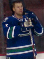 Ice hockey player visible from the waist upwards. Holding his stick vertically down and wearing gloves, a sweater, and no helmet, he has a curious look, focusing on something in the distance.