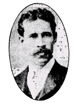 Man with short dark hair parted in middle with long moustache wearing a suit in an oval frame