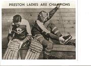 two women putting on hockey equipment