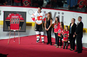a man is pictured along side his wife and three daughters as he is presented with a framed hockey jersey with the numeber 1000 on its back.