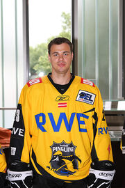 An ice hockey player standing directly in front of the camera, He has brown hair. He is wearing a yellow and black uniform with a large blue RWE and a black and yellow penguin on his chest.