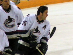 A Caucasian hockey players skates on the ice without his helmet in a relaxed fashion. He is looking to the right and is dressed in a white jersey with blue and maroon trim.