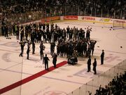 The members of an ice hockey team collectively raise a trophy in celebration while numerous dignitaries and members of the media surround them.