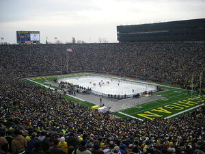 A hockey rink is set up in the middle of a football field, with thousands of people surrounding the playing surface