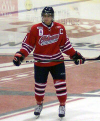 A hockey player, wearing a red Oshawa Generals jersey, stands in full gear on ice with stick held across his waist.
