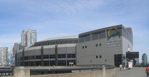 A grey building with two distincive sections. The section on the left curves in a circular manner away from the viewer. The lower half is composed of windows. The section on the right is shaped like a square and has windows only in the bottom-left corner. A yellow circle and two jagged green shapes resembling triangles are at the top-right of the square building, with the words General Motors Place written in white capitals directly beneath. Several skysrapers are visible in the background.