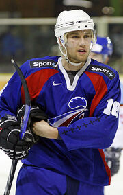 An ice hockey player holds his stick in one hand while removing his glove of his left hand. He is wearing a white helmet and a blue and red uniform with a roosters head on his chest.