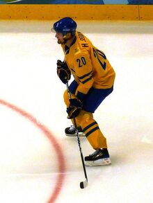 An ice hockey player dressed in a yellow and blue jersey holding his hockey stick in a ready position.