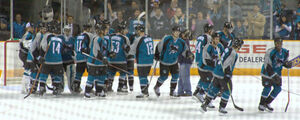 Sharks team members lined up on the ice after a game congratulating their goaltender on a win.