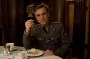 Christoph Waltz with a strudel and smoking a cigarette