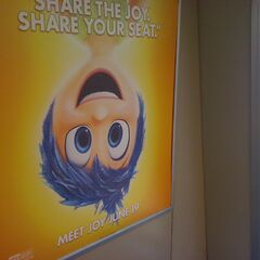 An ad for <i>Inside Out</i> featuring Joy seen on a BART train during the film's first week of release.