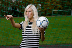 Blonde woman with black and white stripped clothing with a football ball and a whistle