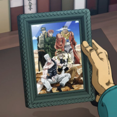 Jotaro, in his office, holds the photo of his old friends