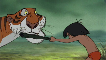 Mowgli is beating up Shere Khan the tiger with a stick
