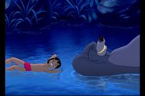 Baloo the Bear and Mowgli are both in the river