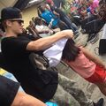Justin Bieber giving a shirt to a kid