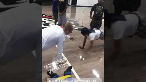Justin Bieber doing push-ups with a child