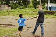 Justin Bieber giving pencil to kid