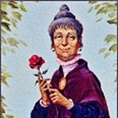 Une vieille femme (Constance Hatchaway, la mariée meurtrière) tenant une rose est assise sur une grande pierre tombale, au fond de laquelle se trouve un buste en pierre de son mari George avec une hachette dans la tête.