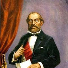 Un homme barbu (Alexander Nitrokoff) tenant un document ne porte que ses sous-vêtements à partir de la taille et se tient debout sur un baril de dynamite allumé.