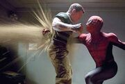 Spider-Man punches Sandman, and his fist is seen on the other side of his chest, with sand blowing through the hole