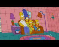 Los Simpson se sientan en la galeria de un estadio y levantan unas pancartas con la imagen de ellos sentados en el sofa