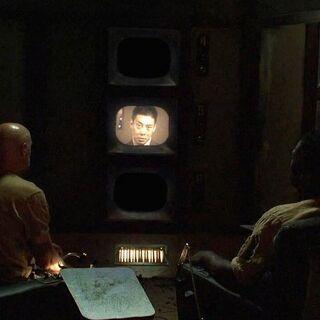 Locke e Mr. Eko assistindo ao Vídeo de Orientação da Estação Pérola