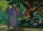 Mowgli and Shanti are both on Baloo the bear's shoulders