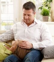 7136712-mid-adult-woman-expecting-baby-lying-on-sofa-in-smiling-man-s-lap-man-stroking-her-head-other-hand-o