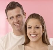 19355327-young-couple-smiling-happy-hugging-woman-showing-pregnant-tummy