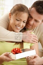 6711726-portrait-of-happy-couple-embracing-looking-down-at-present-in-woman-s-hand