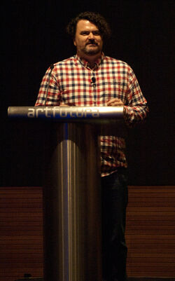 A middle aged Caucasian man with dark hair speaks from a lectern.