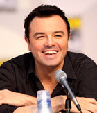 A man with black hair, and tan skin with a black shirt on, leans forward while laughing into a microphone.