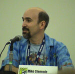 """A Caucasian bald man with a black beard looks to the left while speaking into a microphone. A plaque with the Comic-Con logo on the table reads """"Mike Stemmle""""."""