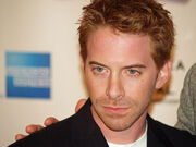 A young man with red hair, and stubble, looks slightly to his right. He is wearing a black jacket, and white shirt.