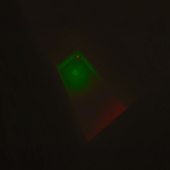 The hole leading down into the Green Box, with a player sitting down in the corner.