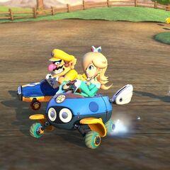 Rosalina, Wario, and Metal Mario race on the track.