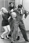 1954-Bud-Collyer,-the-show's-stunt-master,-offers-his-services-as-Doris-Haley-and-Jim-Holland-try-to-force-a-balloon-past-his-elbow-without-its-bursting.