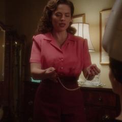 Carter le coloca a Underwood el collar.