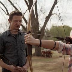 Lila es entrenada por su padre en el tiro con arco.