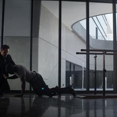 Rhodes es ayudado por Stark a caminar con un nuevo dispositivo.
